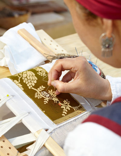 High angle view of woman embroidering fabric