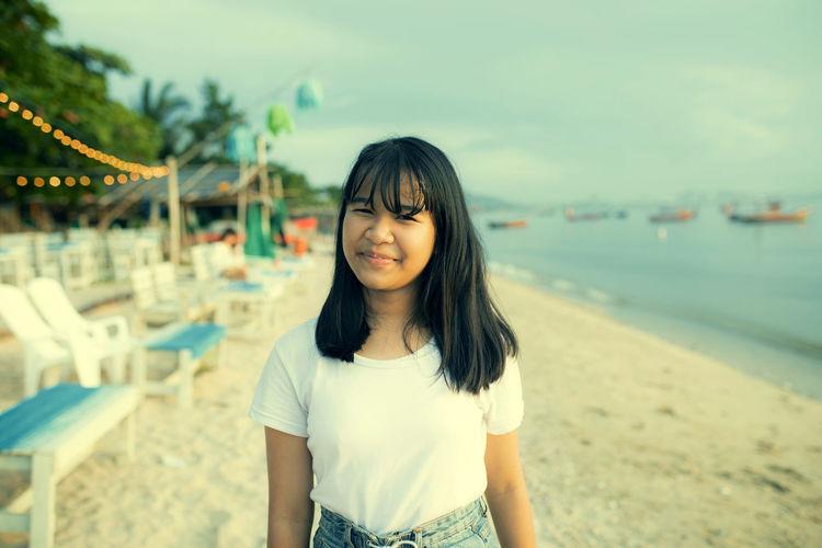 Portrait of girl standing on beach against sky