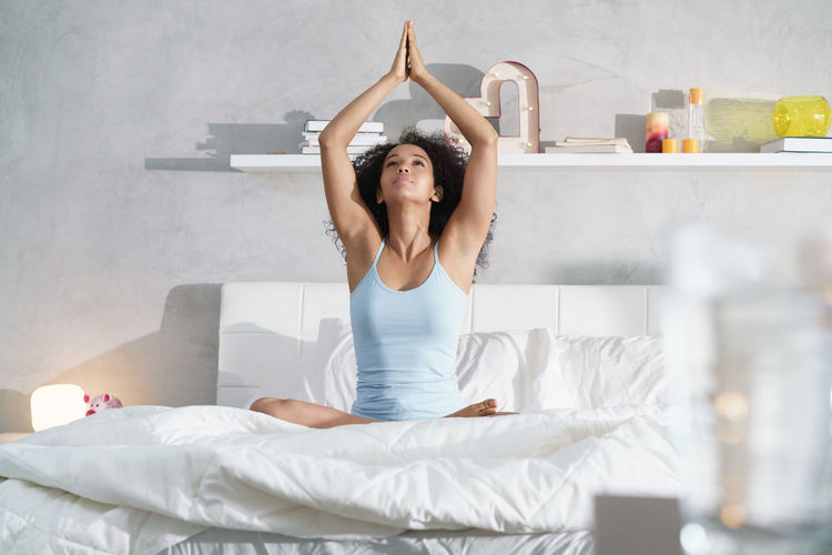Full length of woman relaxing on bed