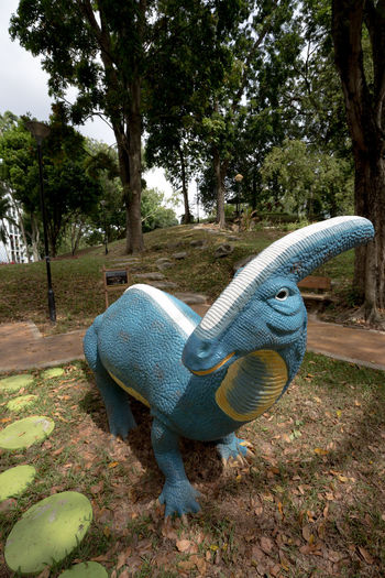 Dinosaur Playground - Parasaurolophus Public Playground Dinosaur Dinosaur Playground Animal Animal Representation Animal Themes Art And Craft Childhood Day Field Green Color Growth Land Nature No People Outdoors Park Park - Man Made Space Playground Representation Sculpture Tree