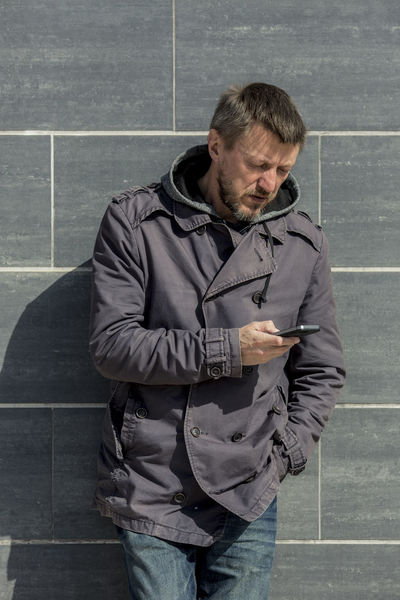Man standing near the wall and looking at smartphone. 45-50 Mobile Phone Wall Adult Caucasian Clothing Communication Day Front View Gray Holding Hood - Clothing Leisure Activity Lifestyles Males  Men One Person Real People Smartphone Standing Technology Telephone Three Quarter Length Waist Up