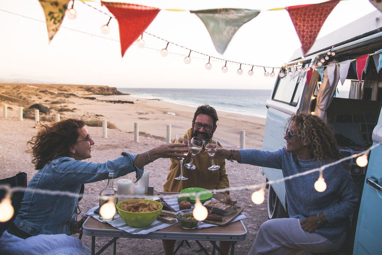 Happy friends cheering and drinking wine during camping vacation at the beach with vintage van. People having fun at weekend summer evening with camper. Youth lifestyle togetherness and party concept Beautiful Brunch Caucasian Celebrating Celebration Cheers Countryside Decorations Dinner Drink Easy Eating Enjoy Excursion Family Festive Flags Food Free Time Freedom Friendship Garden Glasses Grill Group Having Hipster Laughing Leisure Lights Lunch Meal Men Nature Outdoor Outdoors Park person Pic Nic Picnic Red Relax Restaurant Toasting Together Travel Vineyard Winery Young