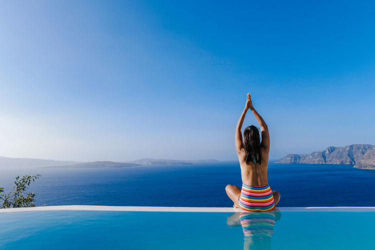 Woman practicing yoga in swimming pool against sea