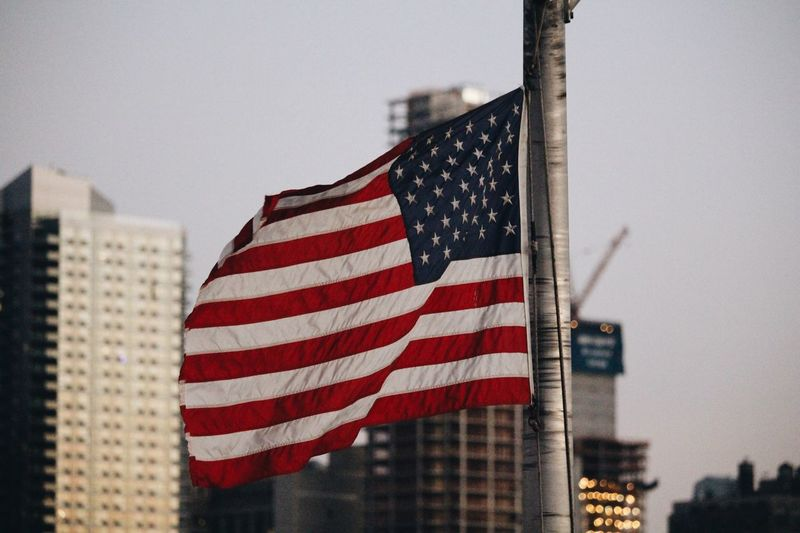 Close-Up Of American Flag Against Buildings In City