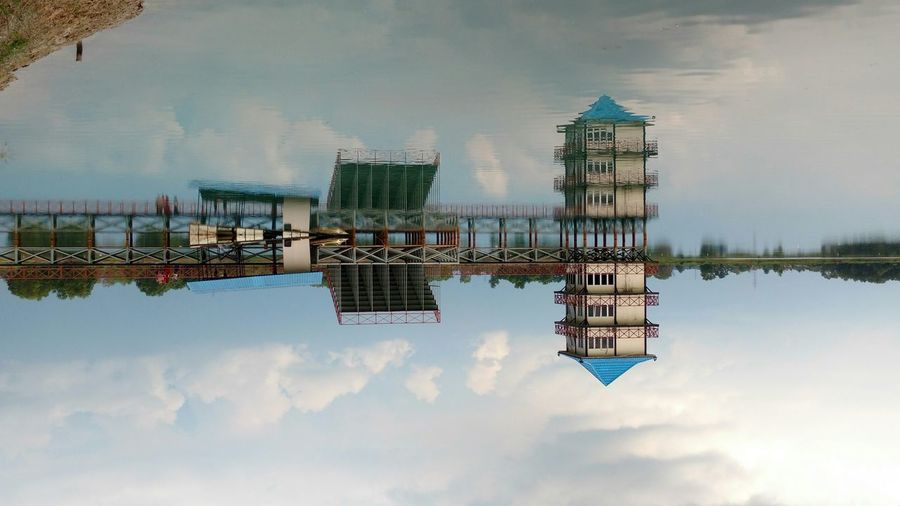 Upside Down Image Of Building Reflecting In Lake