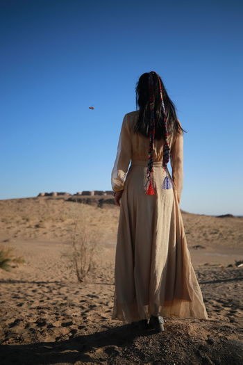 Rear view of woman standing on land against clear blue sky