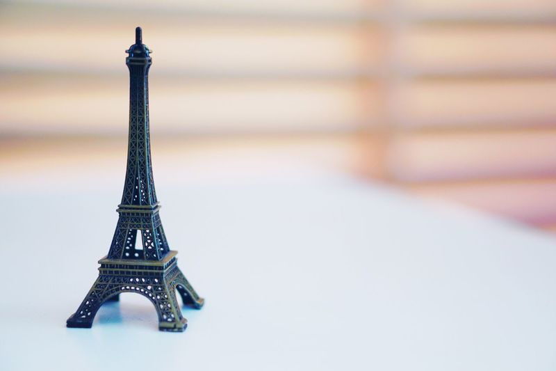 Eiffel Tower model on white table and wooden blind blurred background, Trip souvenir Vacation Dream Toy Model Eiffel Tower Souvenir Built Structure Architecture Metal Tower Travel Destinations Tourism Close-up City Travel Table