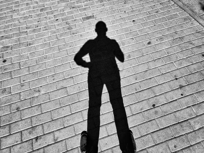 Shadow of man walking on footpath