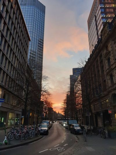 City street amidst buildings against sky during sunset