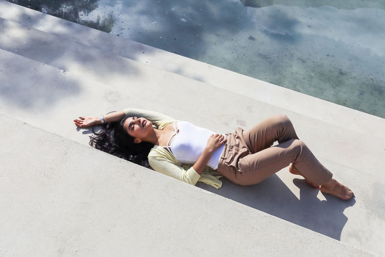 High angle view of woman lying on steps outdoors