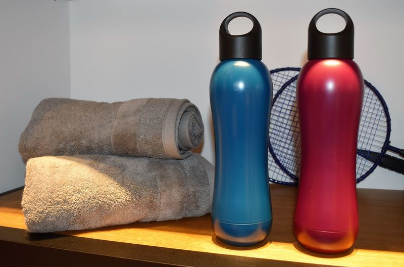 Close-up of bottles by towels on table