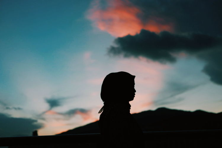 Silhouette woman looking at sunset sky
