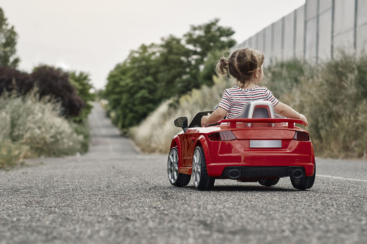 Rear view of boy toy car on road