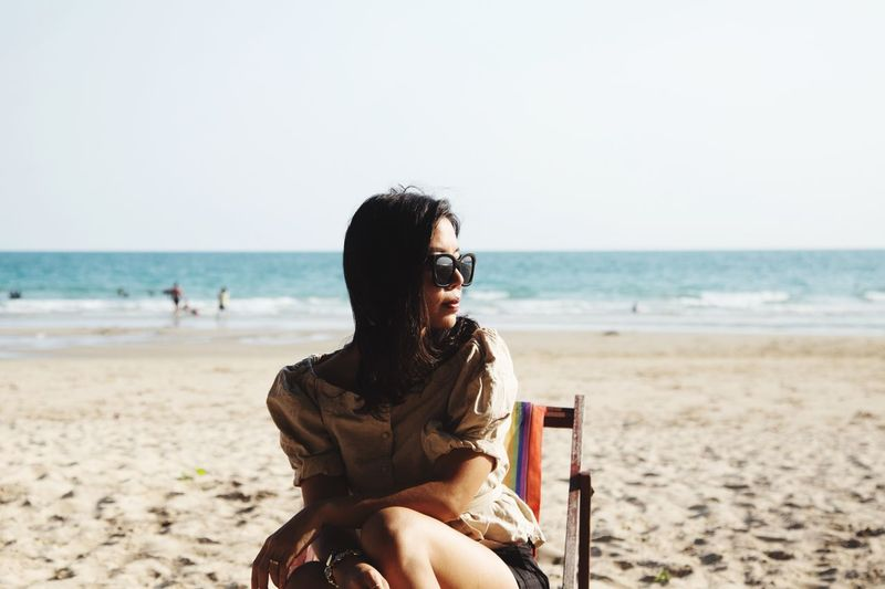 Woman sitting on chair beach against clear sky