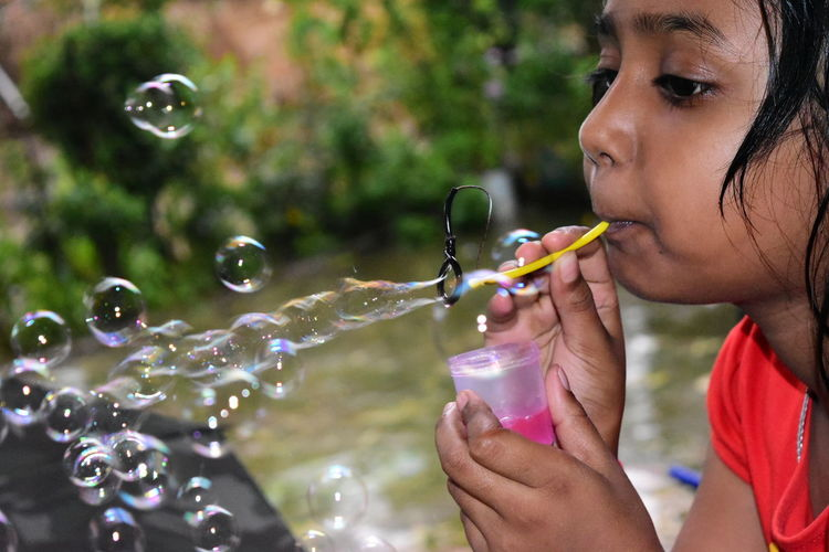 Side view of girl blowing bubbles while standing outdoors