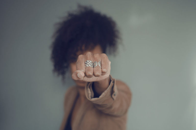 Closeup and selective focus on a black woman fist with rings. afro puff hair.