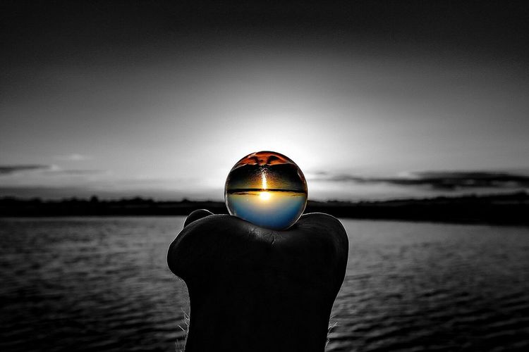 Cropped hand holding glass ball with upside down reflection on sea against sky