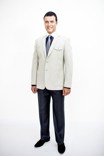 Man in classic suit on the white background. Studio shot. Business Business Stories Adult Business Finance And Industry Businessman Clothes Clothing Confidence  Emotion Formalwear Front View Full Length Indoors  Looking At Camera Males  Men Menswear One Person Portrait Smiling Standing Studio Shot Well-dressed White Background Young Adult