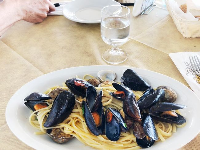 Linguini with mussles, meal ready to eat in italy Outdoors Food And Drink Food Freshness Glass Table Mussel Seafood Plate Hand Human Hand Drinking Glass Drink Refreshment Ready-to-eat Close-up