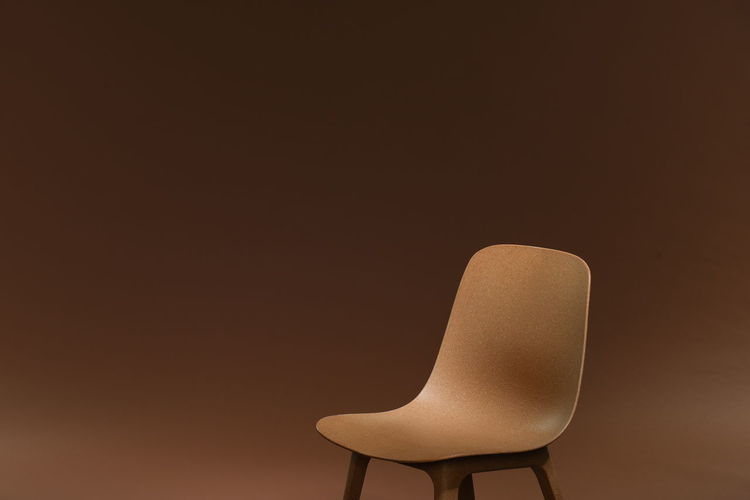 Close-up of empty seat against brown background