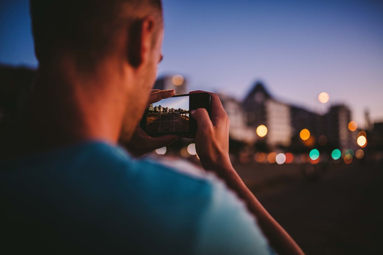 Close-up of man photographing illuminated city