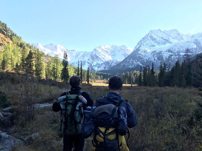 Rear view of male hikers looking at snowcapped mountains against blue sky