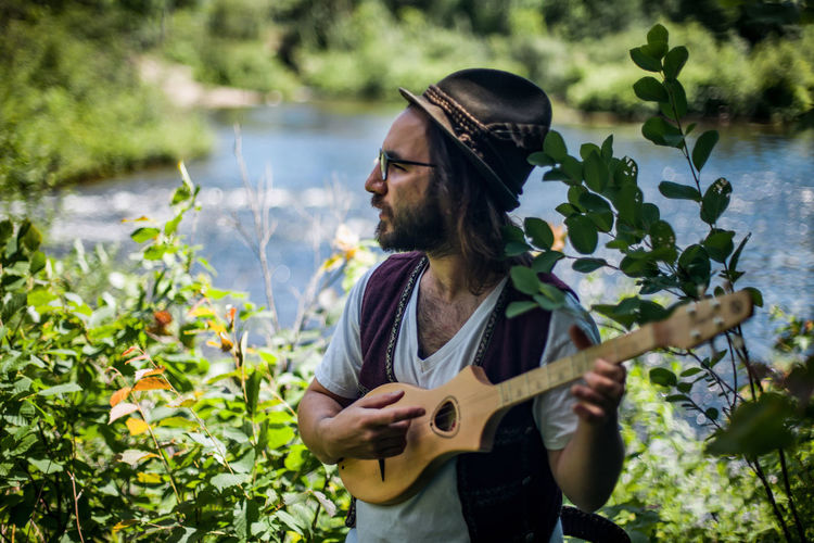 Man playing ukulele while standing against plants