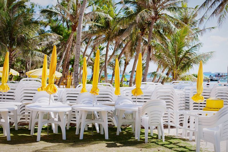 Stack Of Chairs With Parasols On Field Against Trees