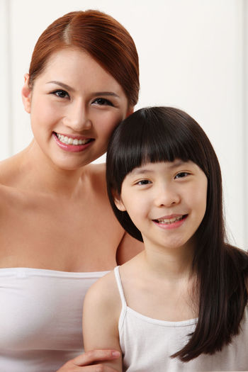 Portrait Of Smiling Mother And Daughter At Home