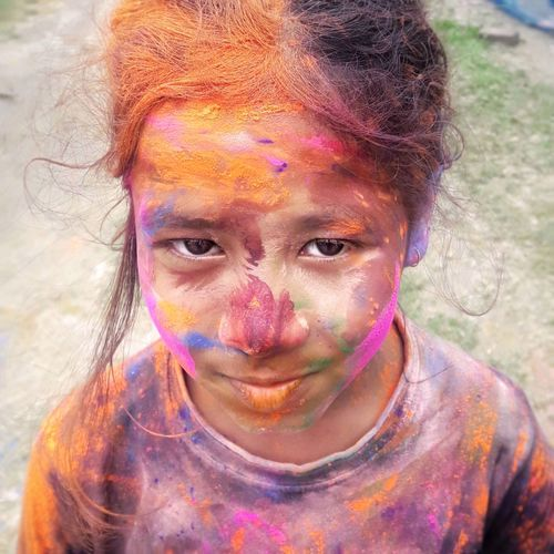 Close-up portrait of smiling girl with face messed in powder paint