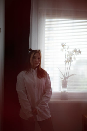 Young woman standing against window at home