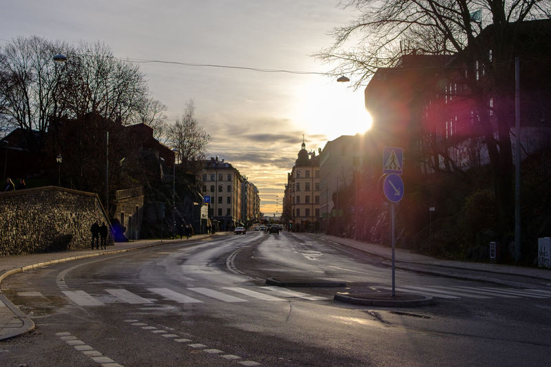 Street in city against sky at sunset
