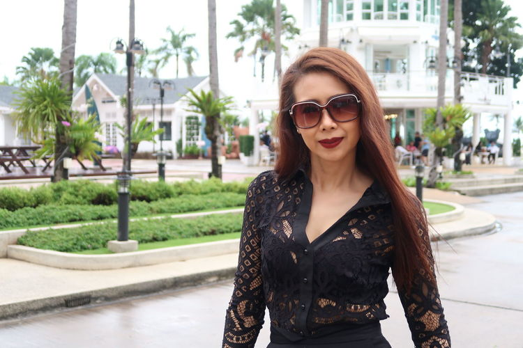 Portrait of smiling woman wearing sunglasses while standing outdoors