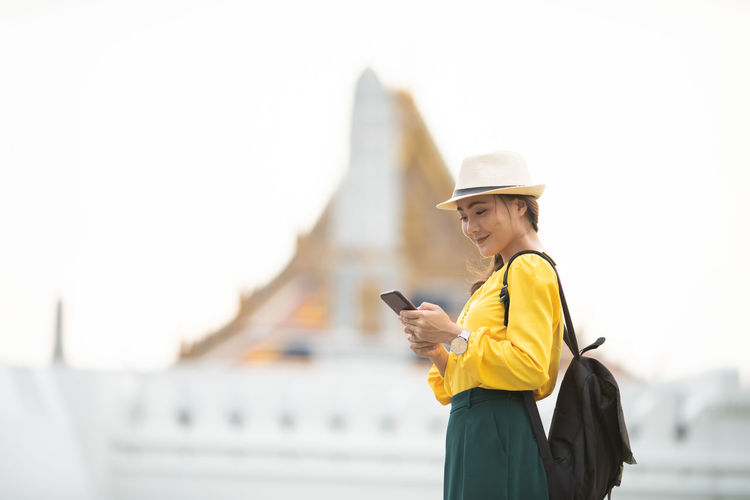 Happy tourist woman used smart phone for searching the street locations Bangkok Thailand Application Architecture Asian  Attractive Backpacker Building Casual Cellular Cheerful City Destination Device GPS Guide Happy Hat Hipster Holiday Leisure Lifestyle Location Mobile Navigation Outdoors Phone Relax Searching Sightseeing Smart Phone Smile Street Summer Sunglasses Technology Tour Tourism Tourist Town Travel Traveler Traveling Trendy Trip Vacation Vintage Weekend Wireless Woman