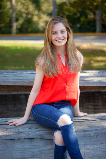 Portrait of smiling young woman sitting on wood