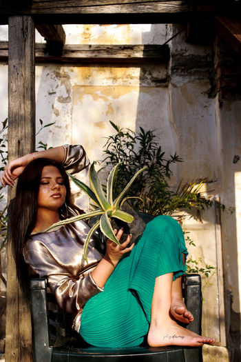 Young woman holding plant while sitting on chair