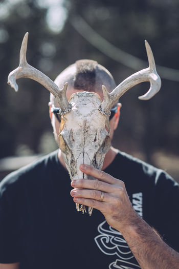 Close-up of man holding animal skull