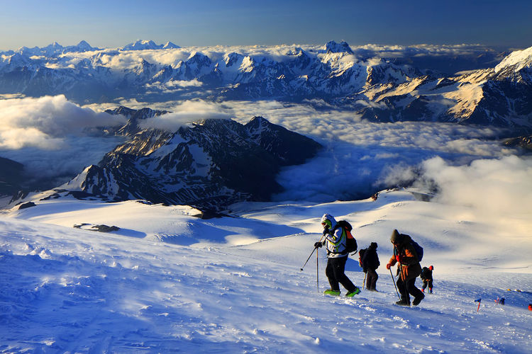 Skiers walking on snowcapped landscape