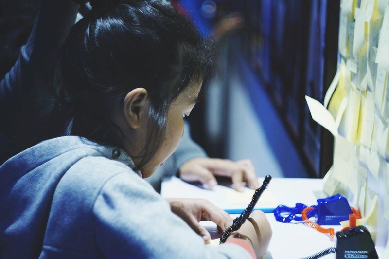 Close-up of girl writing on table