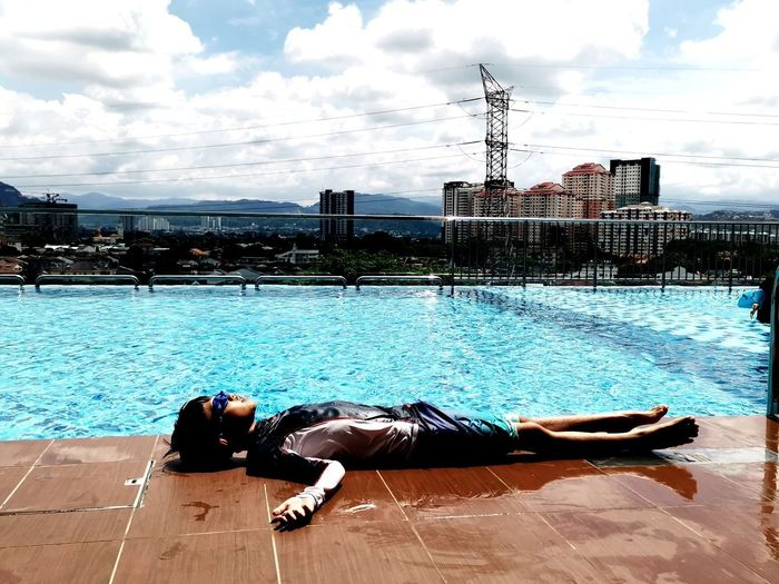 Man lying on swimming pool against sky