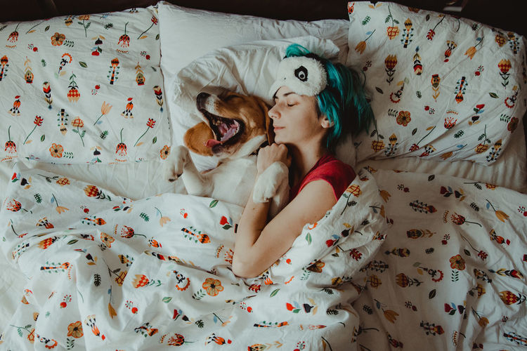 High angle view of woman with dog sleeping on bed at home