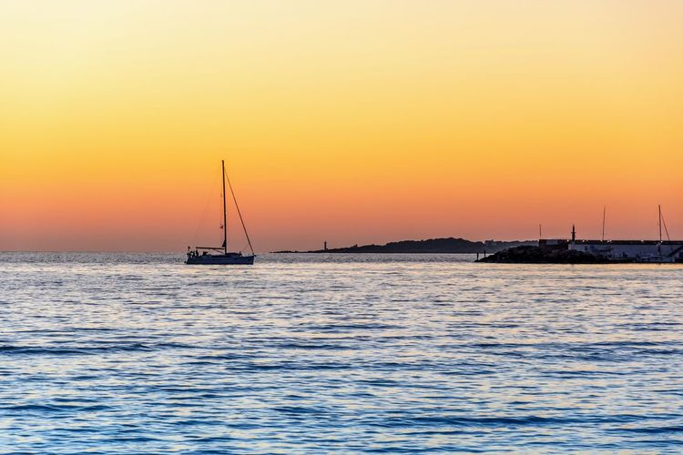 Sailboat Sailing On Sea Against Orange Sky