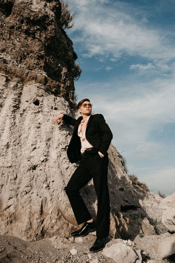 Full Length Of Young Man Wearing Suit Standing On Rock