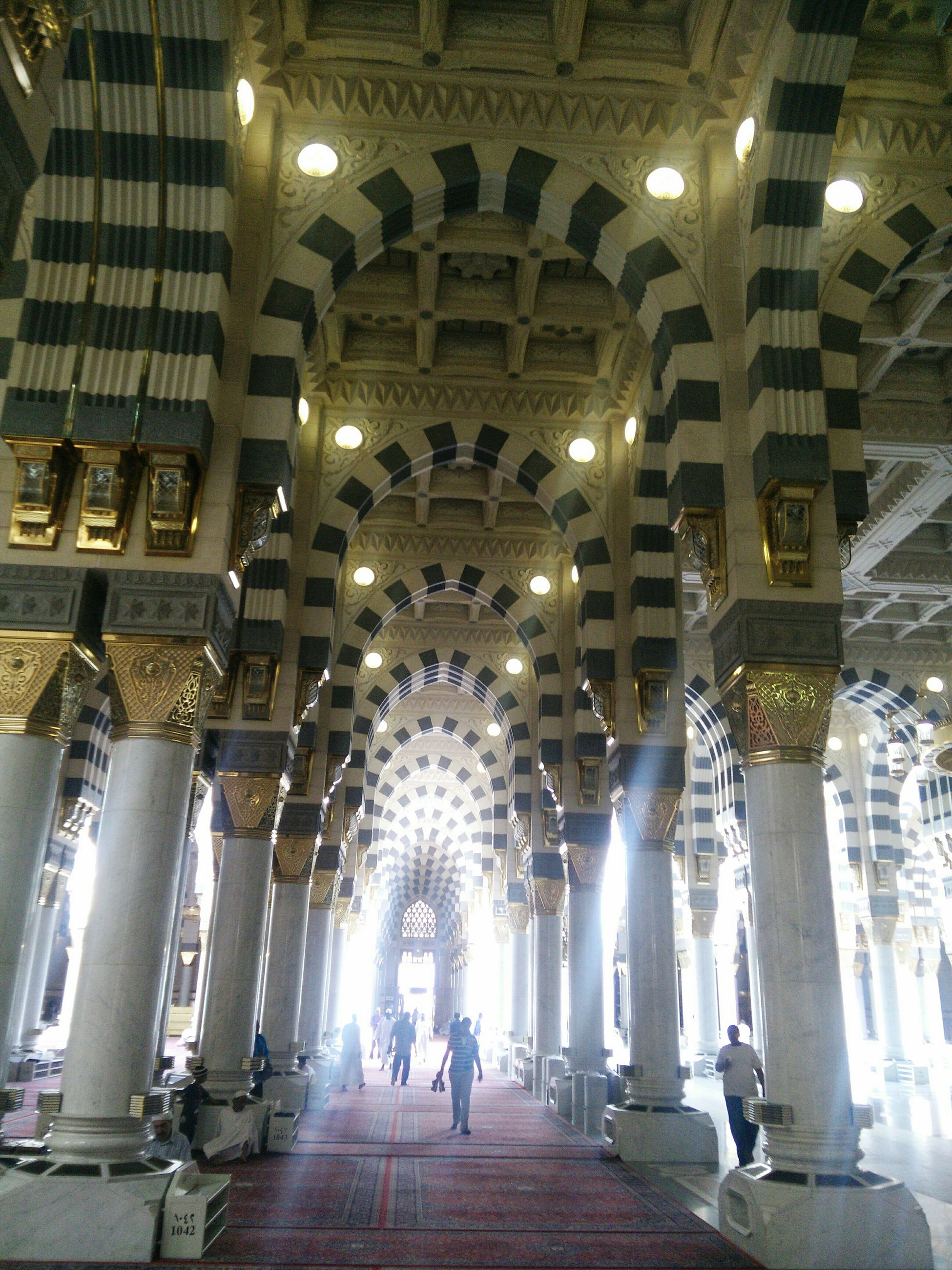 indoors, illuminated, architecture, ceiling, built structure, lighting equipment, architectural column, place of worship, people, night, religion, arch, spirituality, large group of people, corridor, famous place, travel destinations, lifestyles