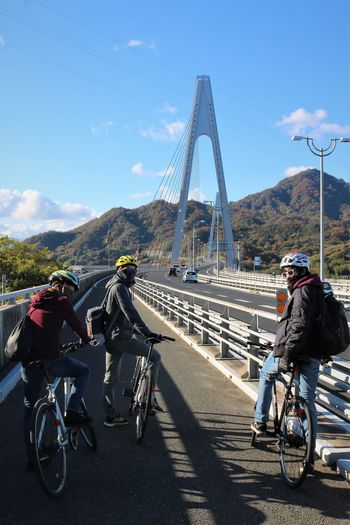 People riding bicycles across cable stayed road bridge