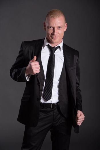 Portrait of businessman against gray background