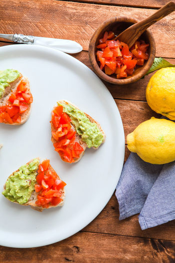 Heart shaped bruschetta with guacamole sauce and chopped tomato. Bread Bruschetta Ignorante Chopped Freshness Guacamole Healthy Eating Heart Shape Messy No People Plate Ready-to-eat Real Life Rustic Tomato Wood Food Stories