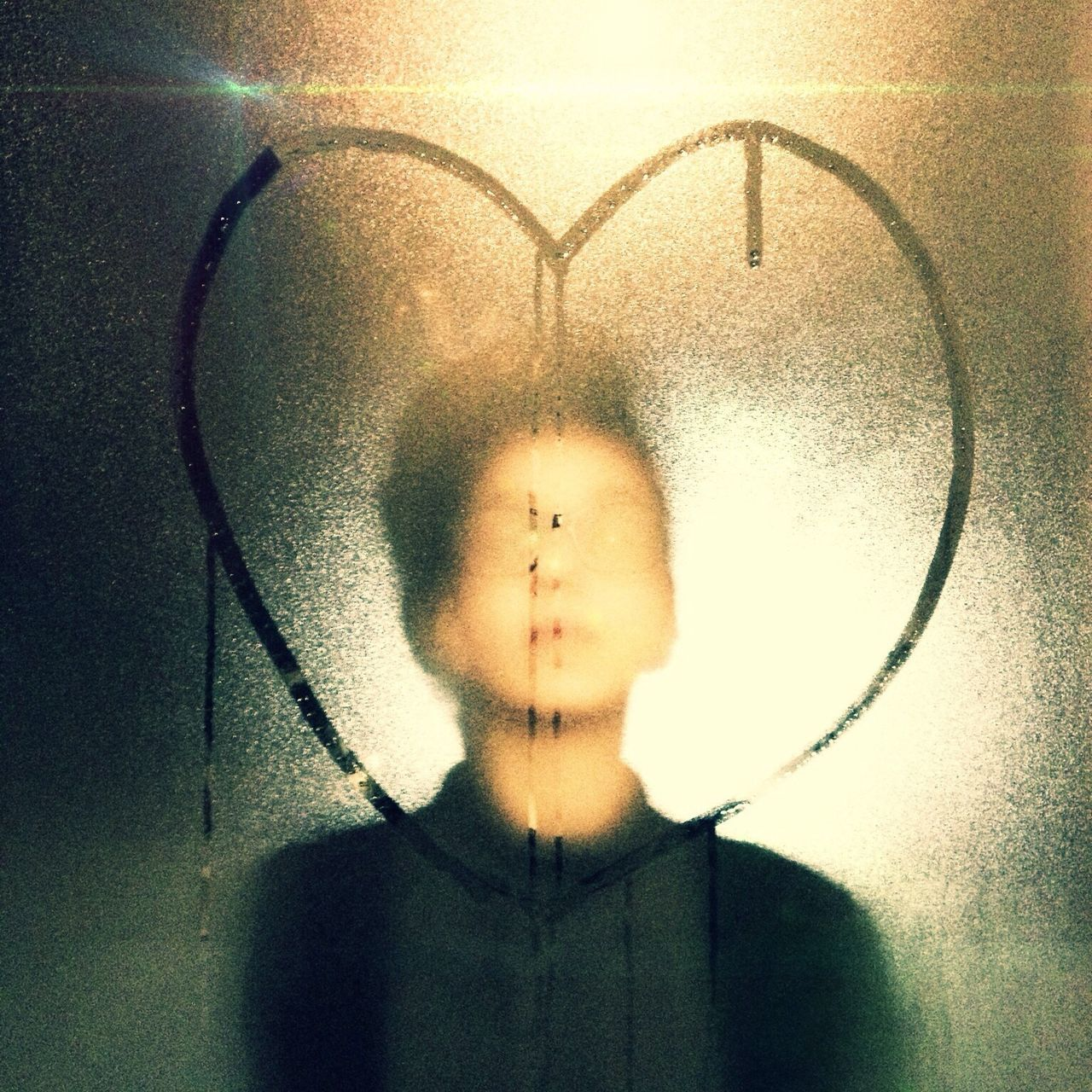 Man standing against heart shape on condense glass