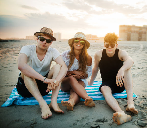 Smiling friends sitting on blanket at beach against sky