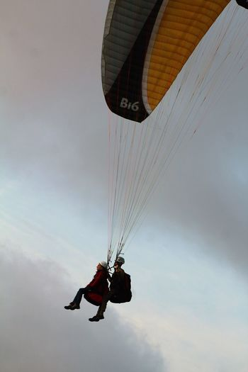 Tourists paragliding in sky